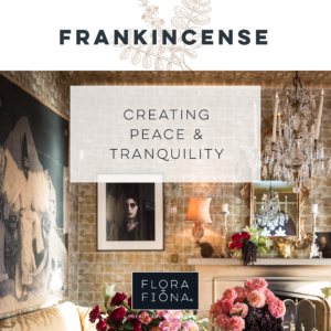 "A luxurious but cosy room has decadent floral and fruit arrangements in both the foreground and background. A painting, a portrait and a mirror hang on two walls while a lamp and candles stand sentinel on a mantelpiece. A chandelier hangs to the right of the frame. Superimposed text reads: ""Frankincense: creating peace and tranquillity."""