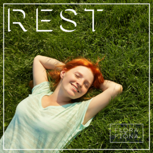 A girl with red hair sleeps happily on green grass. The word REST is superimposed above her.