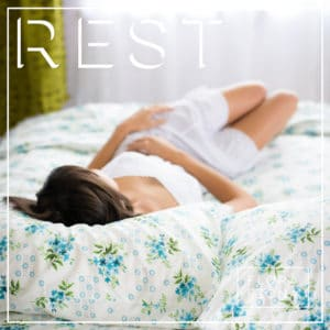 A woman sleeps on a bed with a floral duvet. The word REST is superimposed on the image.